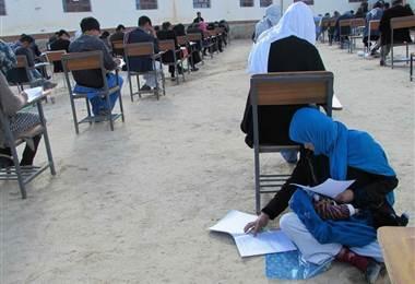 Sentada en el suelo con su bebé en el regazo, Jahantab Ahmadi hace un examen rodeada de estudiantes instalados en pupitres.