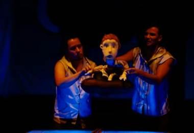 """""""Arena"""" se presenta en el Teatro Vargas Calvo, detrás del Teatro Nacional. Cuenta con un elenco de 3 actores, los cuales interpretan a personajes reales y también dan vida a títeres, quienes abordan de manera sensible el tema de la migración y los refugiados, así como la convivencia entre quienes no hablan el mismo idioma.   """"Arena"""" se desarrolla en una escenografía que recrea el mar, y a pesar de tener elementos infantiles como títeres, la obra también es para adultos. """"Arena"""" se presenta hasta el 23 de septiembre, con funciones los sábados a las 2 de la tarde y los domingos a las 11 de la mañana. Las entradas las puede adquirir en www.teatronacional.go.cr La buena noticia es que los adultos acompañados de niños pagarán su entrada a precio de niño."""