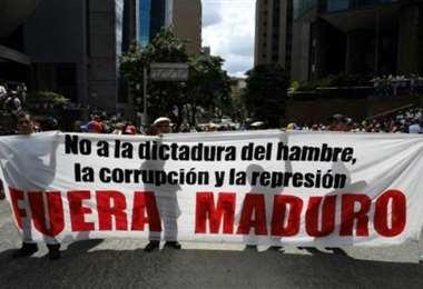 Partidarios del líder opositor Juan Guaidó llevan una pancarta durante una marcha contra el presidente Nicolás Maduro, en Caracas el 16 de noviembre de 2019