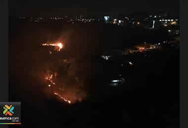 Bomberos intentan controlar quema extensa de charral con amenaza a viviendas en La Uruca
