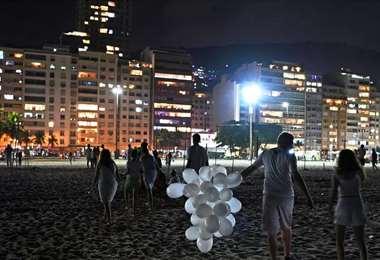 Un puñado de personas celebran el Año Nuevo en la playa de Copacabana, en Rio de Janeiro,